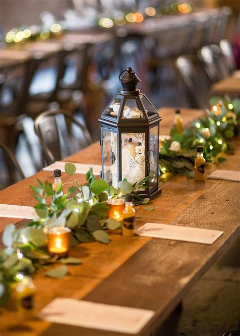 lanters and green garland on wooden tables for wedding