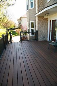 Light Or Dark Deck Stain Shows Light Vinyl Siding Against Brown Brick With The