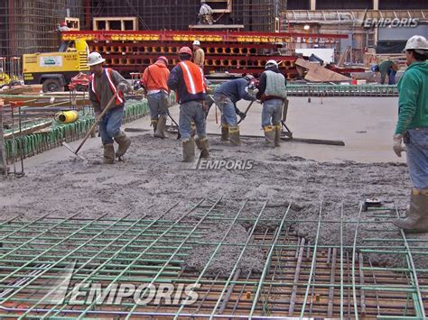 Workers pouring concrete for the ground floor slab on the