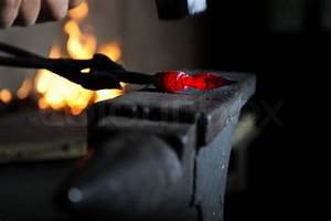 Blacksmith forges a red-hot iron in the forge | Stock ...