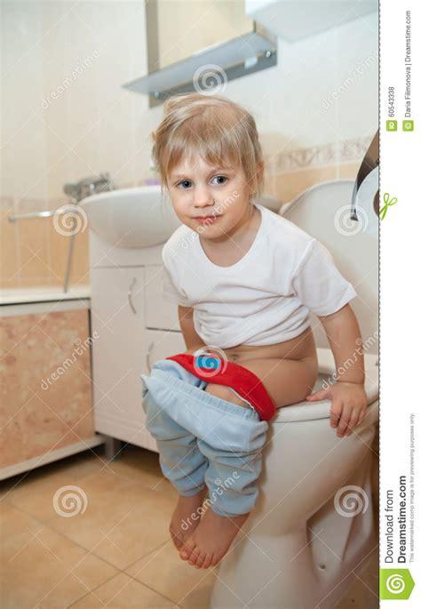fille s asseyant sur la toilette photo stock