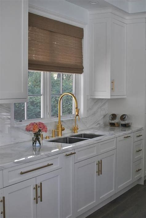 White Kitchen Sink With Stainless Steel Faucet by A Window Dressed In A Brown Bamboo Shade Is Flanked