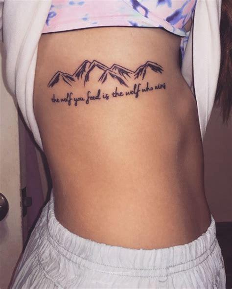 mountain  wording tattoo  girls side rib cage