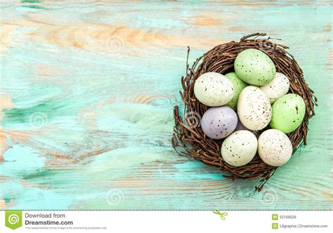 pastel colored easter eggs  nest  wooden background