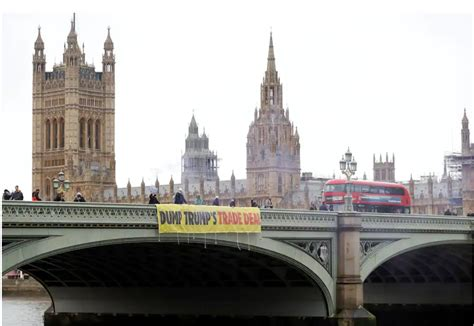 anti trump protesters drape a banner over westminster ...
