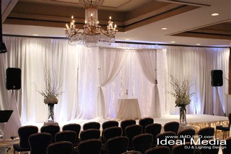 white pipe and drape with uplighting string lights the