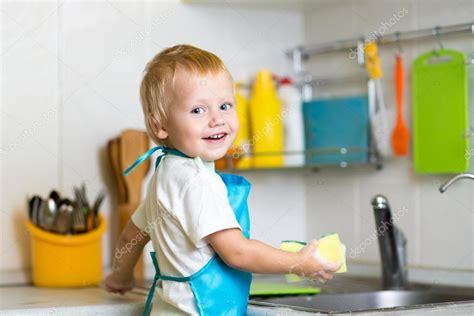 Kleiner Junge hilft Mutter beim Geschirrspülen in der ...
