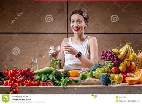 femme a la cuisine eau potable de femme de sport à la cuisine photo stock