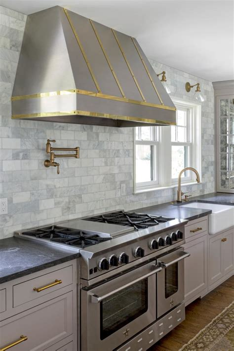 brass lined range hood  subway tile backsplash