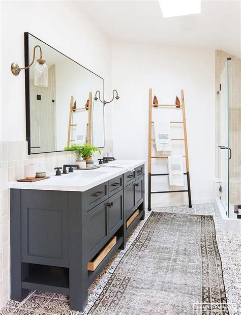 2651 grey bathroom mirror lit by brass and glass sconces a black framed mirror is
