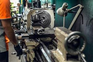 Industrial Worker Operating Cnc Turning Machine In Metal
