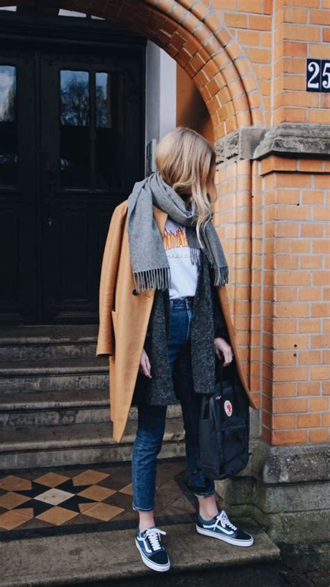 Picture Of blue cropped jeans Vans sneakers a printed tee a grey cardigan a grey scarf and a ...