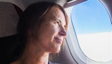 Woman Looks Out Window Of Airplane