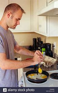 cooking fried eggs for breakfast stock photo alamy