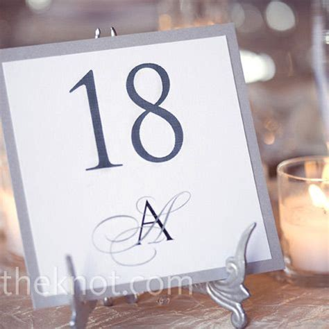 minimalistic table numbers displayed  silver winged