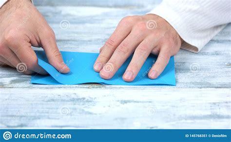 close  hands folding blue paper sheet obraz stock