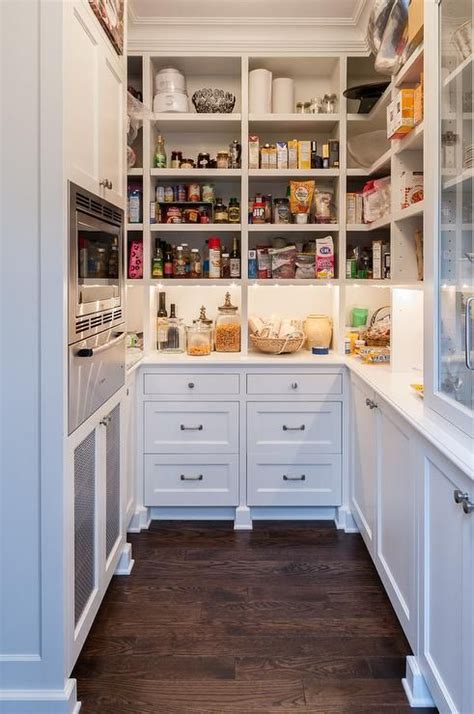 white  shaped kitchen pantry boasts oak floors  custom