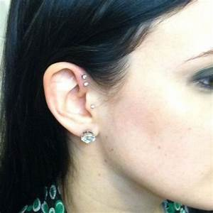Double forward helix piercing, tragus piercing, and ...