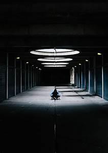 Dark And Light Person Sitting Cross Leg At Hallway Under Glass Ceiling