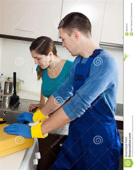 plumber repairing kitchen sink  woman stock photo