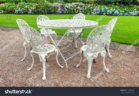 vintage wrought iron garden table and six chairs in an