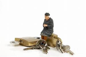 Miniature Figurines Of Elderly Sitting On Padlocks