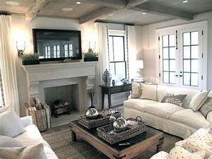 Chic cozy living room with framed tv over stone fireplace for Cozy living room with fireplace