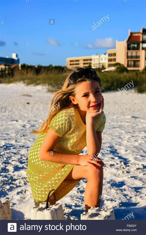 Young Girl Posing At Sunset By The Sand Castle She Built
