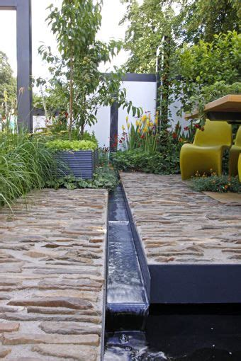 water rill design rill runs between river rock in concrete patios one of which is elevated a bit over the other