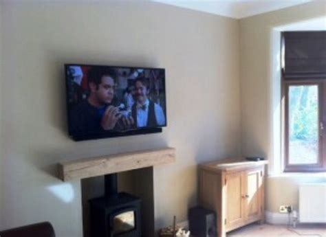 Smart flat screen tv above a wood burning stove with oak