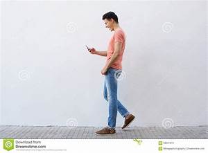 Young Man Walking And Reading Text Message On Cell Phone ...