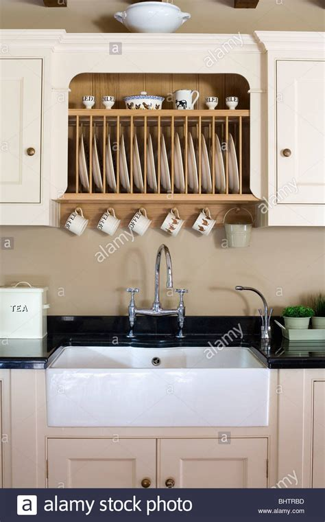 fitted plate rack  fitted cream cupboard  white butlers sink stock photo royalty