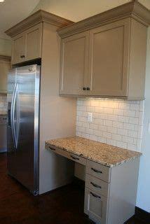 tan painted cabinets  granite tops  subway tile