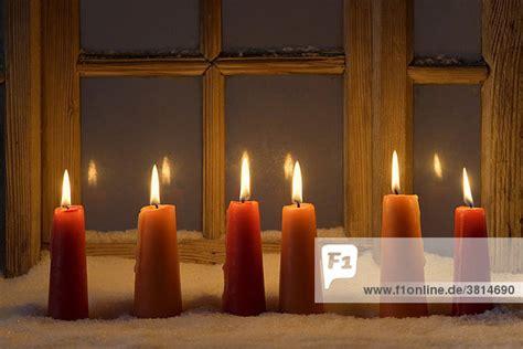 brennende kerzen im schnee vor einem alten fenster advent