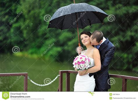 Romantic Wedding Couple Kissing In A Rainy Day Stock Photo