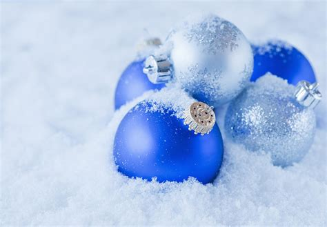 studio shot of blue and silver christmas ornament on snow