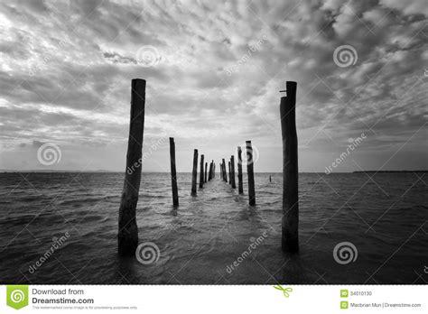 black  white seascape  wooden pillars stock photo