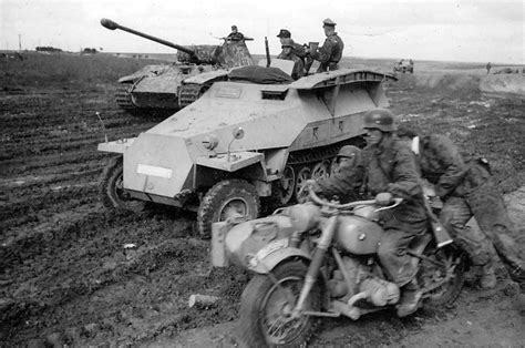 German Soldiers On A Bmw Motorcycle Ride Past A Sd.kfz