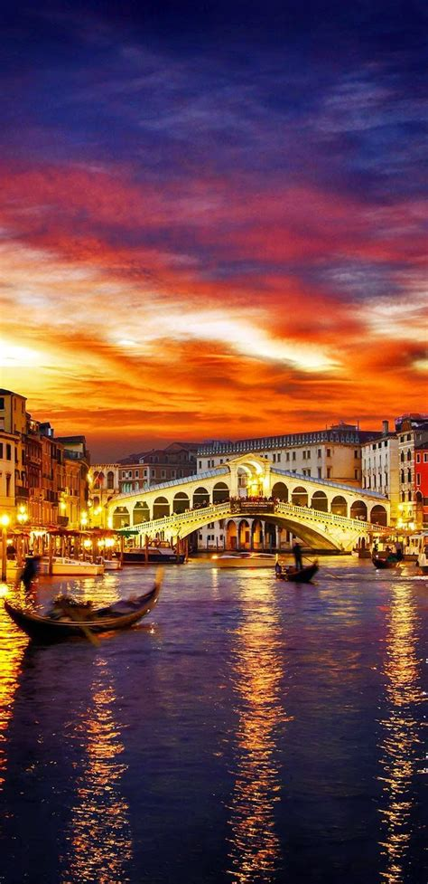 Ponte Rialto And Gondola Bathed In A Golden Sunset In
