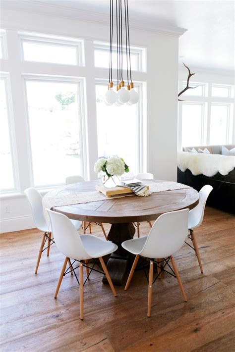 A Rustic Round Wood Table Surrounded By White Eames Dining
