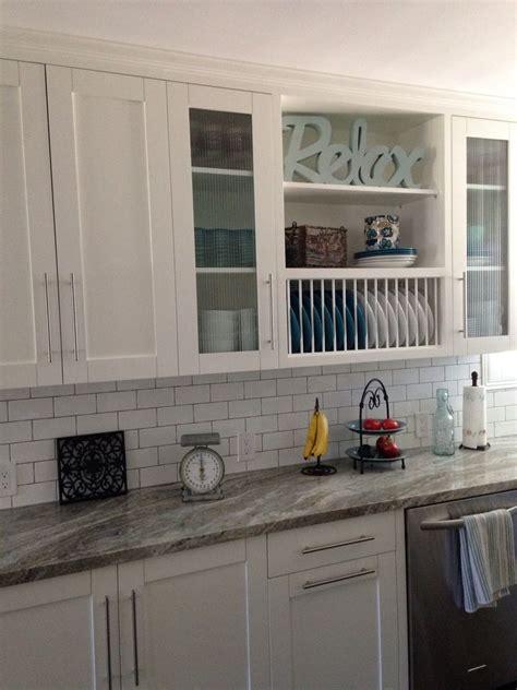 white shaker cabinets  glass doors open shelves plate rack granite counters glass