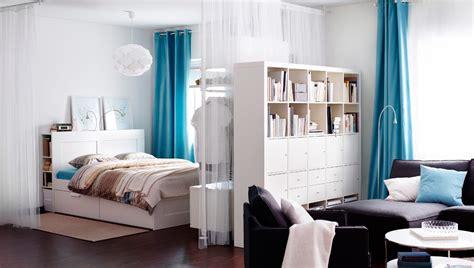 white bookcase dividing space studio apartment room