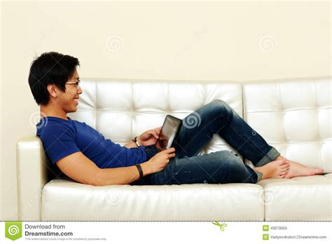 One Person Sofa by Asian Man Lying On The Sofa With Tablet Computer Stock