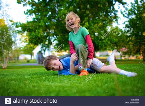 A boy and girl wrestling on the grass; Picton, Ontario ...