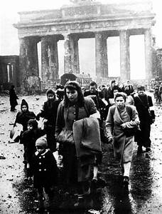 Germany Women and children walk through the ruins of
