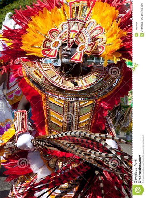 male dancer dressed  orange  red feathers dances
