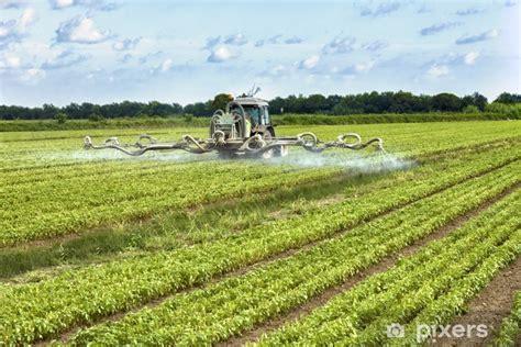 fototapete traktor die pestizide auf einem feld pixers