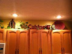 Image result for primitive decorating above cabinets for Best brand of paint for kitchen cabinets with religious candle holder