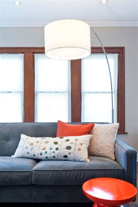 large floor lamp, blue sofa, orange accent stool and