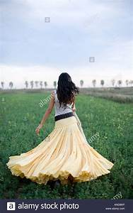young woman running on a green field wearing a long yellow ...
